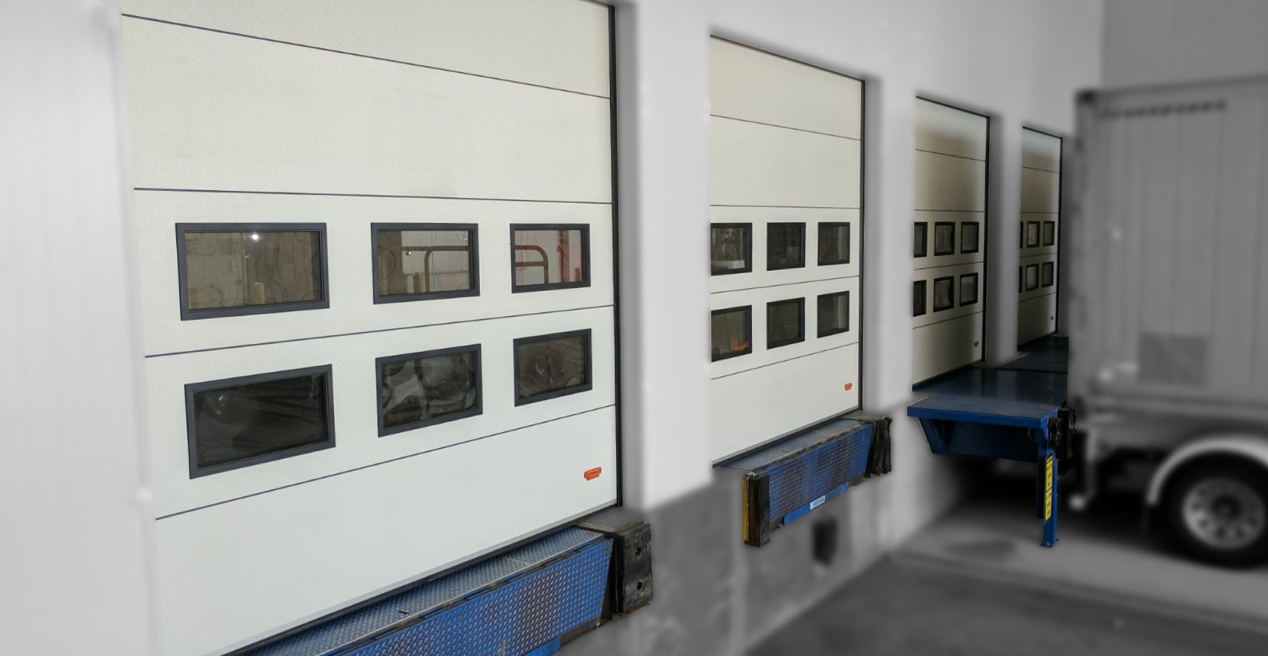 Insulated sectional loading dock doors which fold